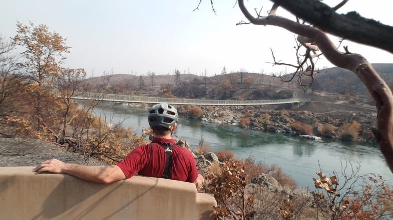landscape image, bridge across Sacramento River, Stressed River Bridge, Carr fire damage across the river. Man sitting on bench looking across the river, Mary J McCoy-Dressel Books, #WordlessWednesday blog post