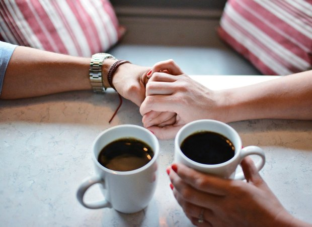 Blog post First Love Book Hooks, Mary J McCoy-Dressel, couple having coffee. Holding hands across the table. Two coffee cups