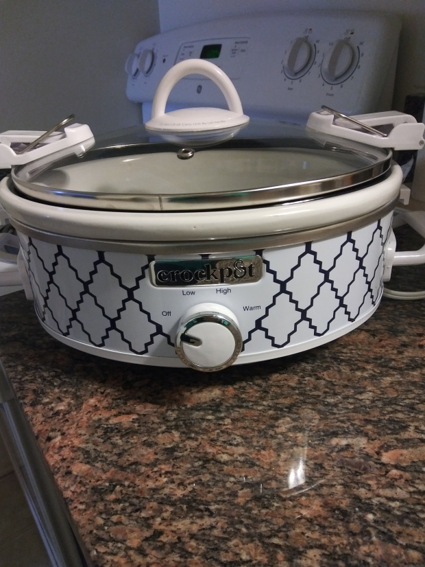 Crockpot brand crock pot. White with a blue diamond shape design covering the bottom half. Clear top with white handles. Lid locks on the top.